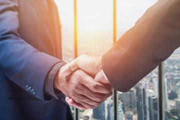 Successful businessmen handshaking after good deal.