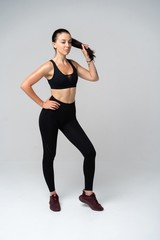 Young fit woman in sports outfit, studio photo.