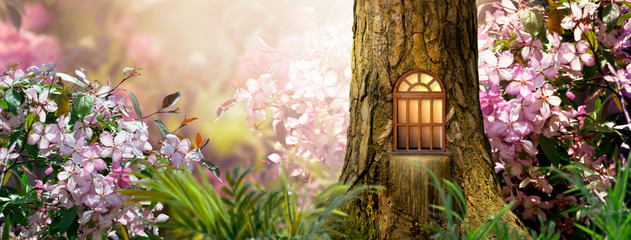 Enchanted fairy tale forest with magical shining window in hollow of fantasy pine tree elf house, blooming fabulous giant pink sakura cherry flower garden, building in wood in fairytale morning light