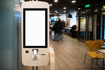 Self-service desk with touch screen in fast food restaurant