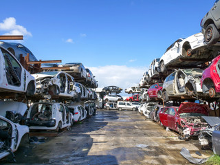 Large Salvage Car parts and Vehicles lot, with rows of stacked totalled Cars