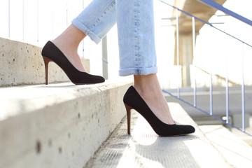 Profile of woman legs wearing high heels walking down stairs