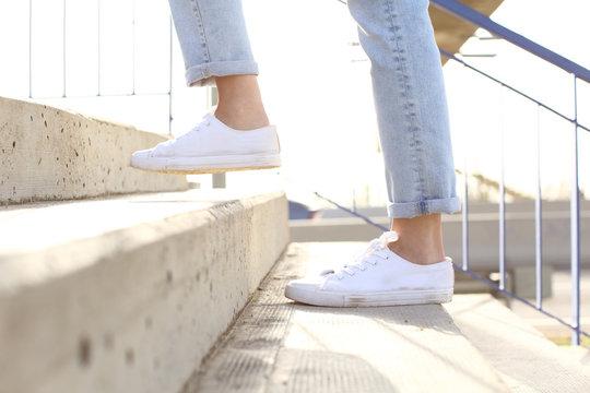 Profile of woman legs wearing sneakers walking up stairs