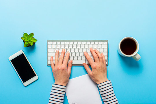 Woman works in the office on a blue background.Only hands Concept workspace, working at a computer, freelance, design. phone, flower, pencil. Banner. Flat lay, top view