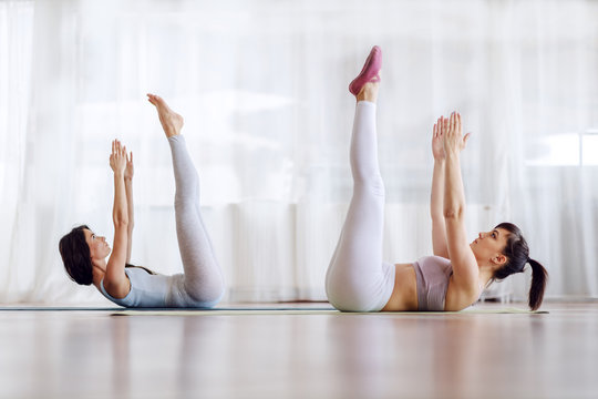 Two beautiful young women lying on the mat in yoga studio with hands and arms in the air.