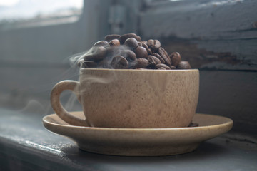 Cup with coffee grains and steam on a wooden background.Close-up.
