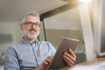 Mature man in office working with digital tablet