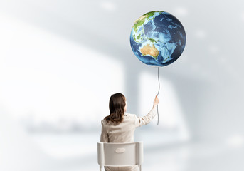 Woman holding by rope earth globe