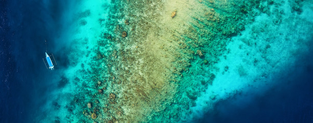 Panoramic view on the coral reef and boat. Azure water background from top view. Summer seascape from air. Travel - image