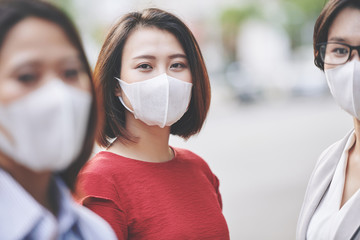 Portrait of beautiful young Vietnamese woman in medical mask standing on the street of her polluted...