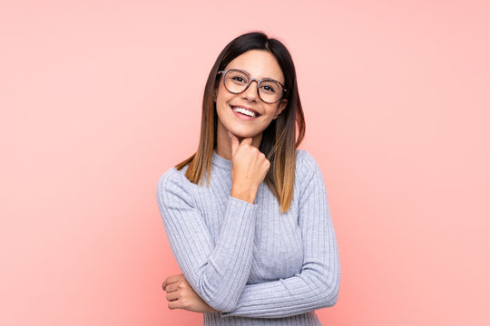 Woman over isolated pink background with glasses and smiling