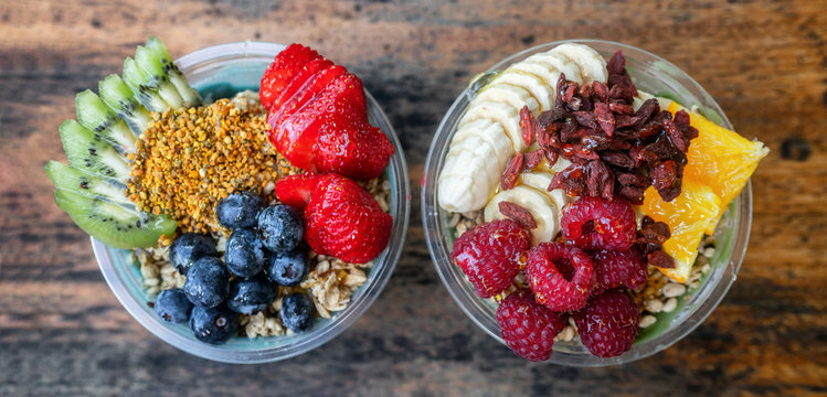 Acai bowls top view banner panoramic of healthy food breakfast smoothie bowl at restaurant. Two fruit cups filled with spirulina, kiwi, goji berries summer eating.