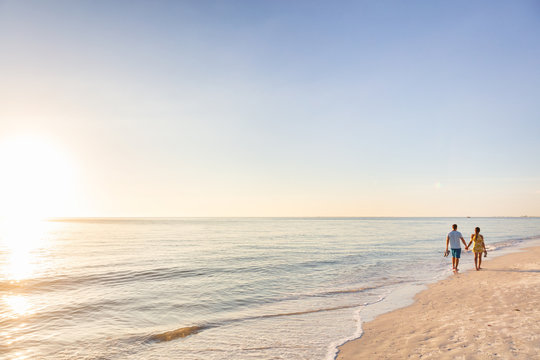 Beach relaxing vacation - travel tourists couple walking on beach at sunset landscape background. Summer holidays destination.