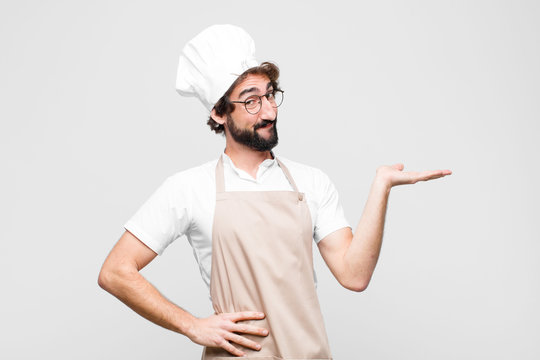 young crazy chef smiling, feeling confident, successful and happy, showing concept or idea on copy space on the side against white wall