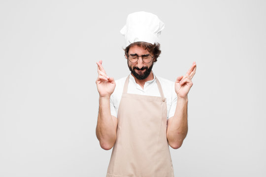 young crazy chef feeling nervous and hopeful, crossing fingers, praying and hoping for good luck against white wall