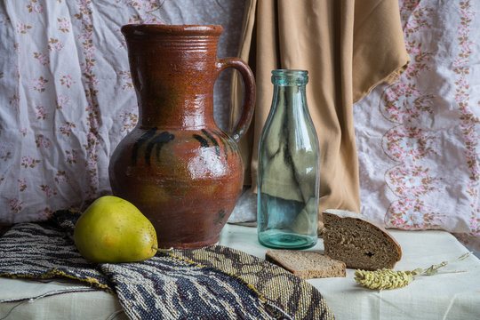 Still life with a jug, a bottle, a pear and rye bread. Russian style of painting
