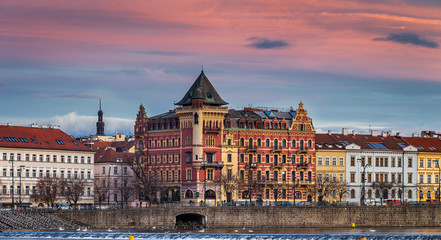 Prague, Czech Republic - Panoramic view of the riverside of Prague at winter time with traditional buildings, hotels and beautiful purple sky at sunset