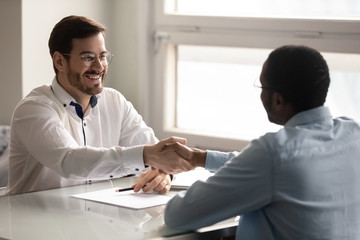 Employer shaking hands starting job interview greeting african applicant