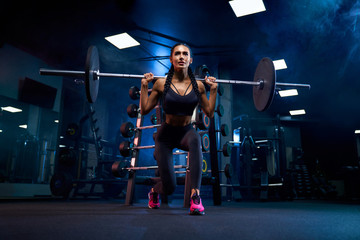 Woman doing squats with barbell on shoulders.