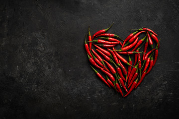Canvas Prints Hot chili peppers Spicy red chili pepper in the shape of a heart on a dark stone background, design concept for Valentine's day