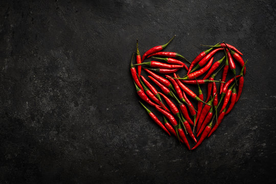 Spicy red chili pepper in the shape of a heart on a dark stone background, design concept for Valentine's day