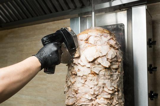 Chef hands chop chicken for doner kebab