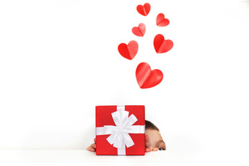 a young man holding a present box with red hearts on a white background. child covers his face with a box