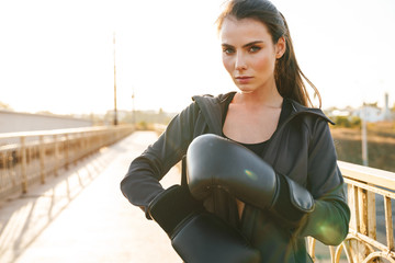 Woman boxer in gloves posing outdoors.