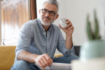 Foto auf Acrylglas Kaffee Man at home sitting in sofa having hot coffee