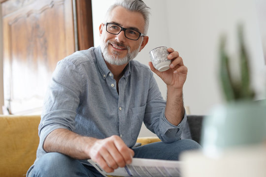 Man at home sitting in sofa having hot coffee