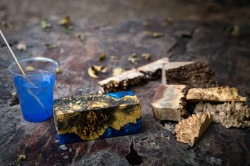 Casting blue epoxy resin burl wood cube on old table art background