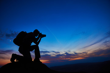 professional photographer silhouette at sunset or sunrise Fotobehang
