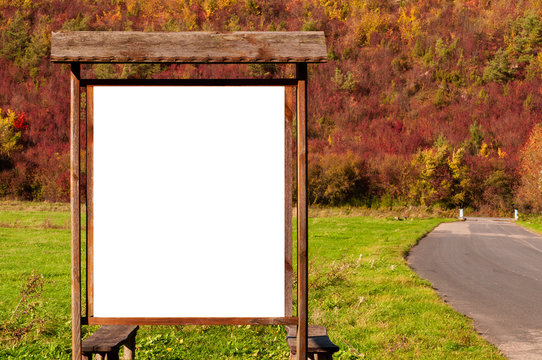 Blank white advertisement/annoucement board on the meadow. Sunny autumn day