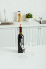 bottle with red wine near empty glasses on white kitchen table