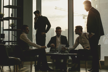 business coworking of young caucasian bearded men in office gathered to discuss business ideas,...