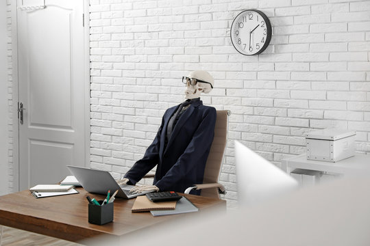 Human skeleton in suit using laptop at table in office