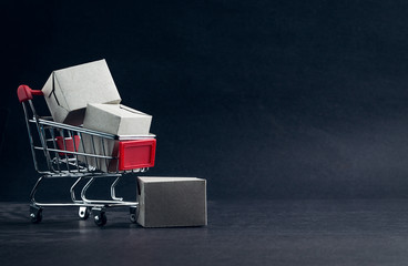 Shopping cart and box on dark background, business, shopping concept. Selective focus