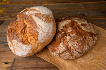 Two fresh whole grain breads from the baker on a jute fabric on a rustic wooden background.