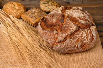 One fresh whole grain bread and and various buns from the baker on a jute fabric with grain ears on a rustic wooden background.