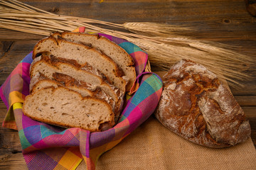 Freshly sliced bread with a bread knife in a basket on a jute fabric placed on a rustic wooden background with grain ears.