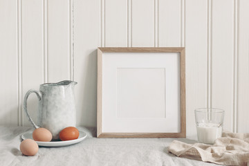 Spring breakfast still life scene. Square empty wooden frame mockup with chicken eggs,, glass of milk and ceramic jug. Easter food and drink concept. Farmhouse, Scandinavian design.