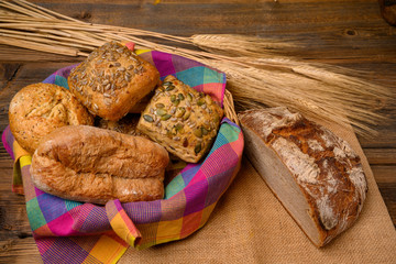 Freshly various buns in a basket and a half whole grain bread on a jute fabric placed on a rustic wooden background with grain ears.