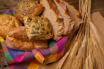 Freshly various buns and bread slices in a basket and a half whole grain bread on a jute fabric placed on a rustic wooden background with grain ears.