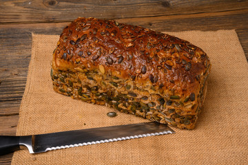 A fresh pumpkin seed bread from the baker on a jute fabric and a bread knife on a rustic wooden background.