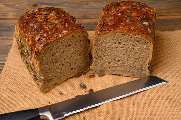 A fresh pumpkin seed bread from the baker halved with a bread knife on a jute fabric on a rustic wooden background.