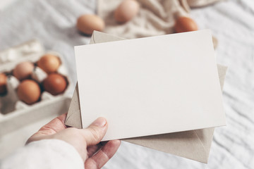 Closeup of woman's hand holding blank paper card. Greeting card mock-up scene. Spring, Easter design. Feminine styled stock photo. Blurred background with chicken eggs and line tablecloth. Top view.