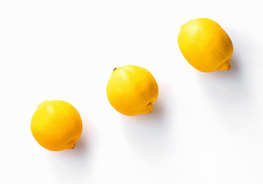 three whole  lemons diagonally with shadow on white background view from above