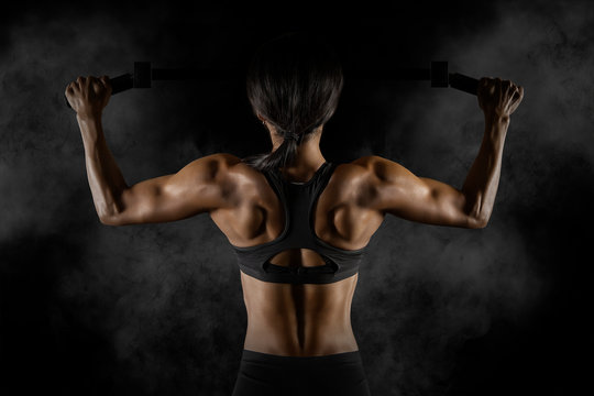 Woman doing pull up exercise on horizontal bar
