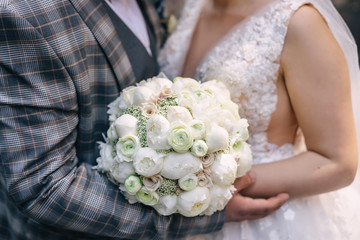 newlyweds are holding a beautiful wedding bouquet of white roses