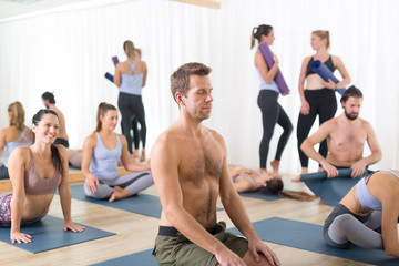 Fotomurales - Group of young sporty attractive people in yoga studio, relaxing and socializing after hot yoga class. Healthy active lifestyle, working out indoors.